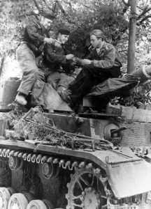 A Panzer MK IV crew from the 21st Panzer Division enjoying some cigars together in Normandy.